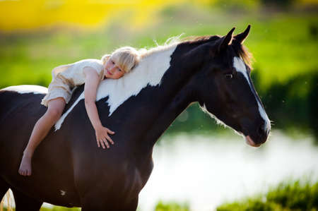 domestic horses: Portrait of child and a horse in filed