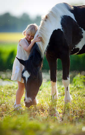Portrait of child and a horse in filed  photo