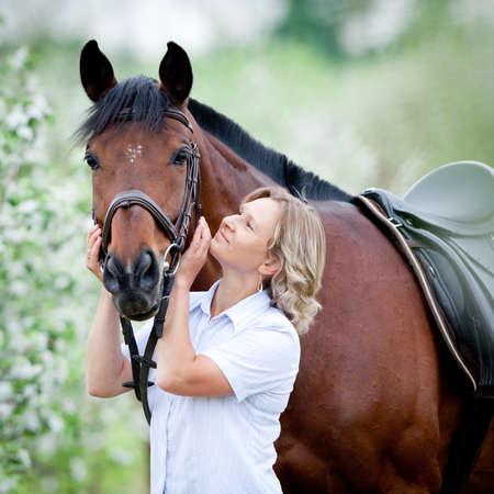 femme a cheval: Femme embrassant un cheval