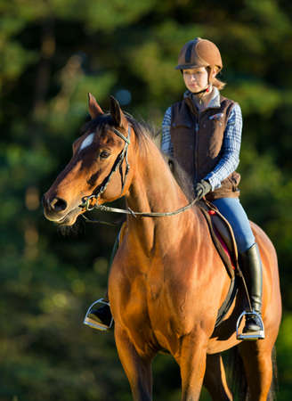 caresses: Young woman riding a horse, horse riding back