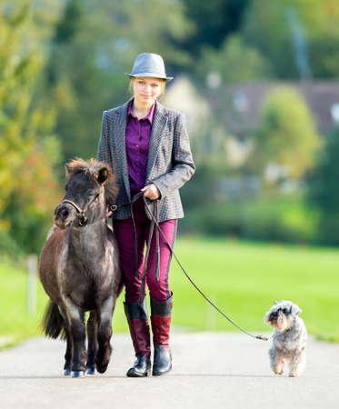 miniature breed: Mujer que camina con el potro y perro