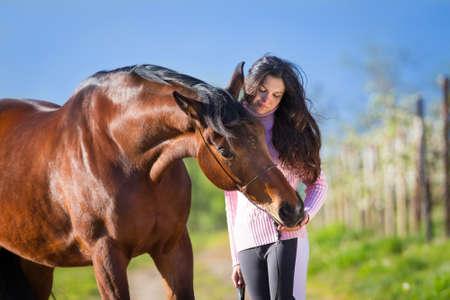 animales de granja: Muchacha hermosa joven de pie con un caballo en el campo