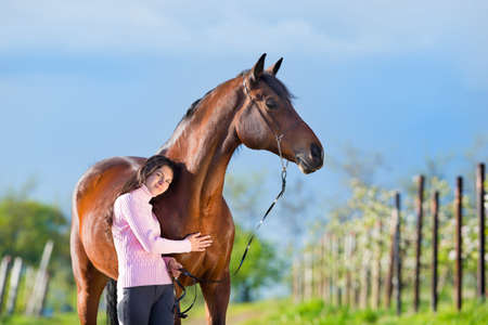 Young beautiful girl standing with a horse in garden photo