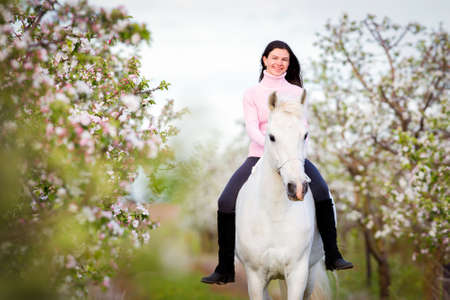 Young beautiful girl riding a white horse in apple orchard