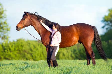 femme et cheval: Belle jeune femme marchant avec un cheval dans le domaine