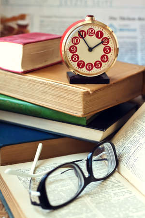 test deadline: glasses, clock and a heap of books