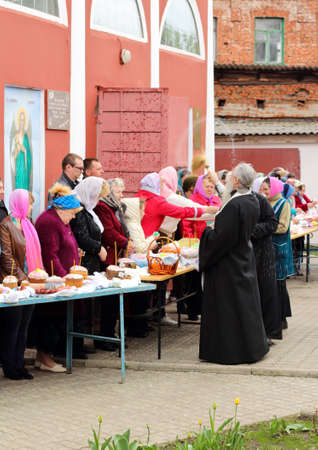 believers: Kursk, 30.04.2016- Russian Orthodox Church priest sprinkle holy water Easter cakes and eggs of believers for Easter in the oldest church of Kursk.