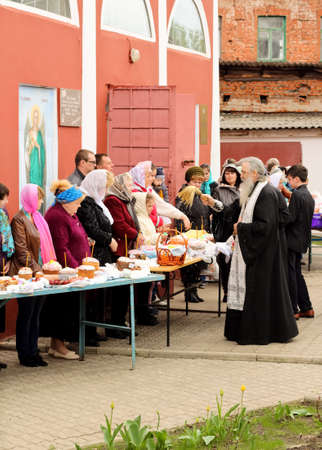 believers: Kursk, 30.04.2016- Russian Orthodox Church priest sprinkle holy water  Easter cakes and eggs of believers for Easter in the oldest church of  Kursk. Editorial