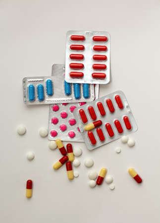 packs of pills: packs of colorful pills in blisters and a lot of scattered pills and capsules around