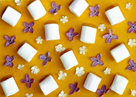 marshmellow: pattern with lilac flowers and white marshmellow on yellow felt background. flat ley. top view.
