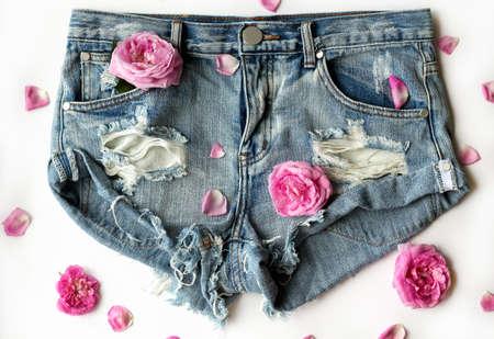 denim shorts: short ripped denim shorts with roses, flat lay