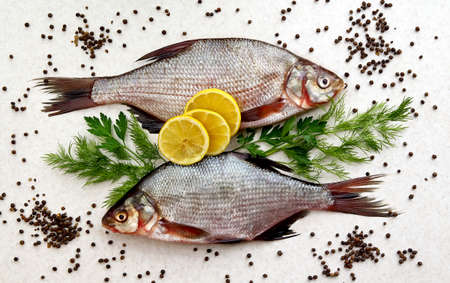 Two raw fresh fishes on marble table with lemon, pepper, dill and parsley. Crucian fishes. top view, flat lay.
