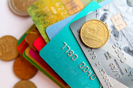waive: stack of multicolored credit cards and euro coins  scattered around, close-up