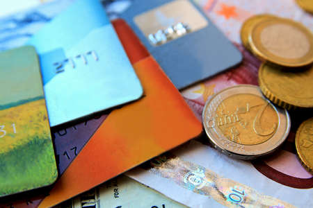 waive: stack of multicolored credit cards and euro coins  scattered around, close-up. Stock Photo