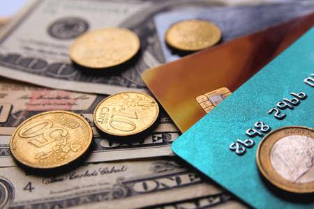 Pile de cartes de crédit avec des dollars américains et des pièces en euros, vue rapprochée.