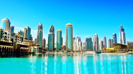 futuristic: Downtown Dubai skyline, panoramic view from the Dubai fountain. Modern city cityscape with skyscrapers, sunny day.