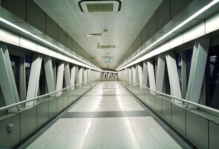 Modern pedestrian overpass air footbridge at night with perspective. Banco de Imagens