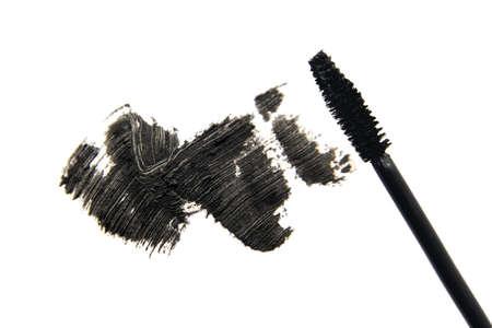 Stroke of black mascara close-up macro with applicator brush, isolated on white background.