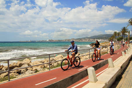 MAJORCA, SPAIN - JUNE 13, 2018: Cyclists riding on the seafront of the Palma de Mallorca. 新闻类图片