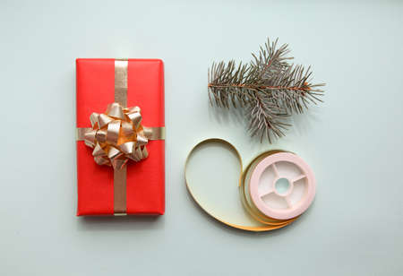 Christmas composition with Christmas gift, pine branche and golden ribbon  on soft blue background, flat lay, top view. Imagens