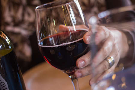 alimentation: Cup of wine and a hand taking it Stock Photo