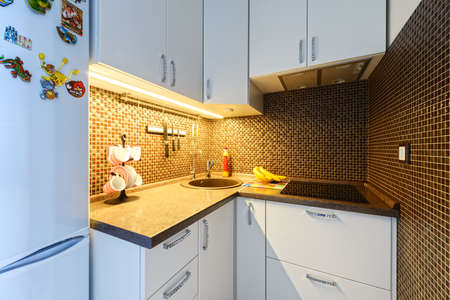 interior desing: Kitchen with white facades and brown tiles
