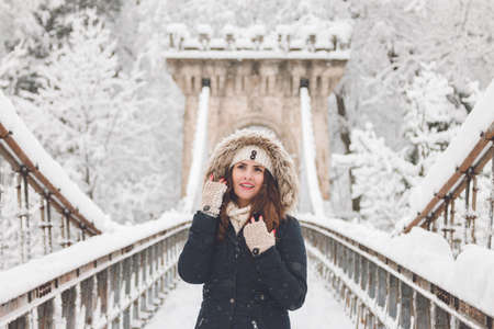 Winter portrait of a beautiful woman in the snowfall