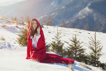 Young woman in red riding hood costume, on a snowy mountain background