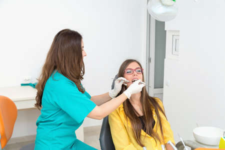 treating: Young woman patient at the dentist, at the dental clinic. Young woman dentist treating her patient Stock Photo