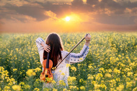 夕暮れ時フィールドでバイオリンを演奏若い女性。伝統的なルーマニア ブラウスを着てうれしそうな少女 写真素材
