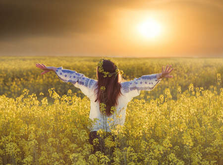 Portrait of a young woman in a rapeseed field. Young joyful girl wearing traditional romanian blouse 版權商用圖片