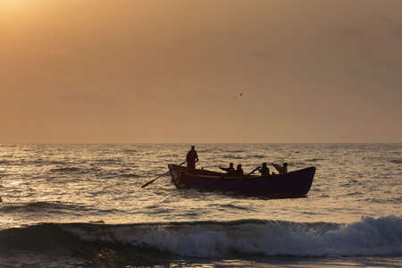 Fishermen silhouettes on boat, at sunrise