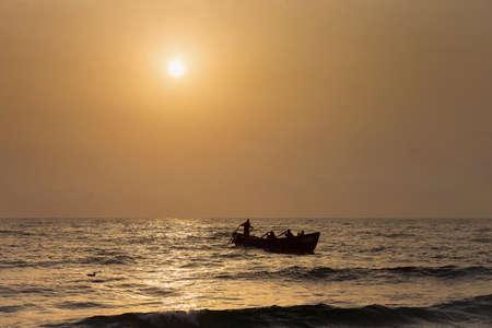 Fishermen silhouettes on boat, at sunrise
