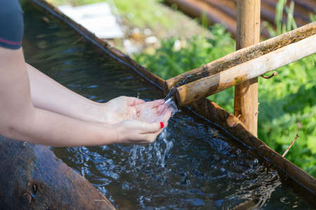 Young woman refreshing her hands in mountain spring