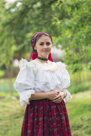 Portrait of a beautiful young woman wearing traditional Romanian clothes, in Maramures Фото со стока