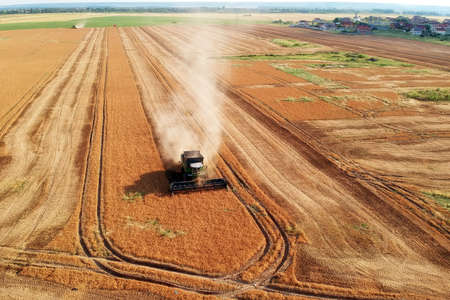 Summer view of combine harvester machine, in the romanian fields. Aerial view of harvesters Imagens