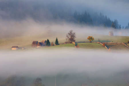 Foggy autumn morning above the traditional romanian cottages