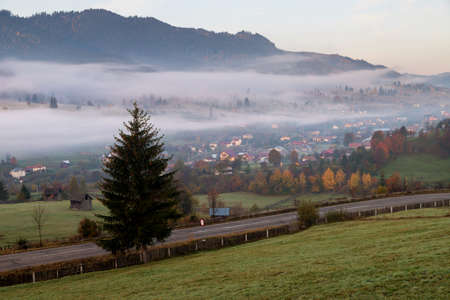 Foggy morning in Bucovina. Autumn colorful landscape in the romanian village 스톡 콘텐츠 - 116785325