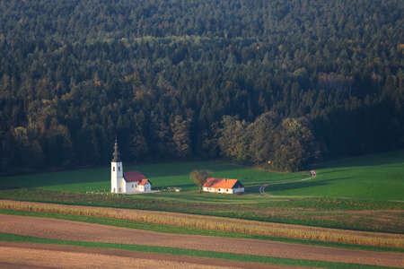 Autumn Slovenian landscape with a beautiful church on a field, at the forest border, near Skofja Loka Banco de Imagens