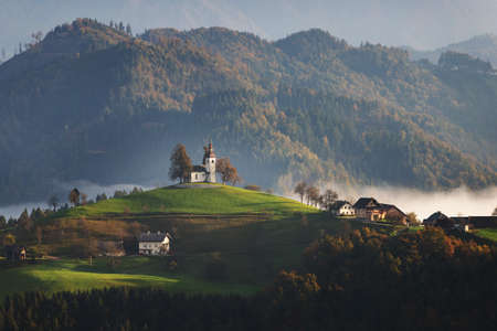 Autumn landscape of a beautiful church on the top of a hill, in Slovenia