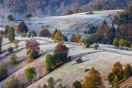 Autumn scene in Romania with hoarfrost over the Carpathian hills, in Transylvania village