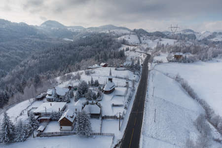 Winter frosty landscape of the beautiful Transylvanian village, Bran, with fresh snow, at the foot of the Carpathian Mountains