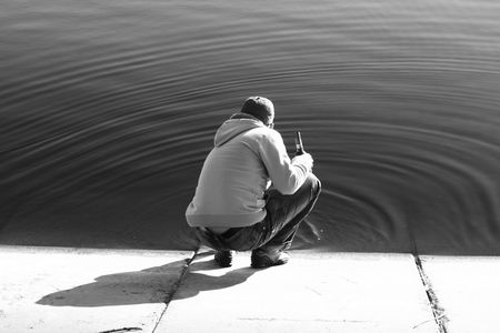 Man on the shore, touching water Stock Photo