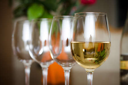 A wine glass with wine and 3 empty ones with a bottle and flowers on the background photo