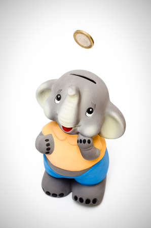 Smilling sweet elephant piggy bank with coin falling into it Stock Photo