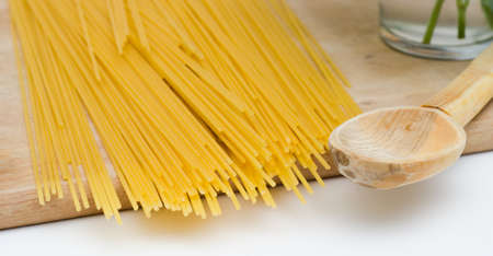 Spagetti on a wooden surface with a wooden spoon ready for cooking