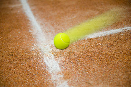 Fats tennis ball hitting court on the line Stock Photo