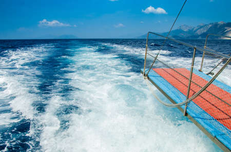 Background view of splash coased by the engine of the boat with blue water photo