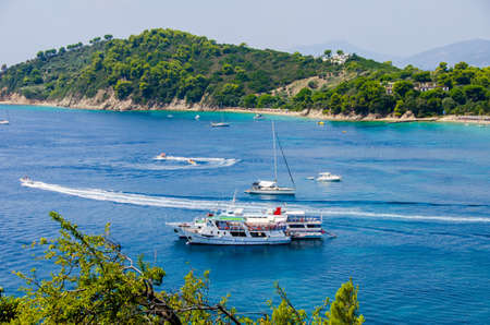 skiathos: Boats on blue water near skiathos with a green background