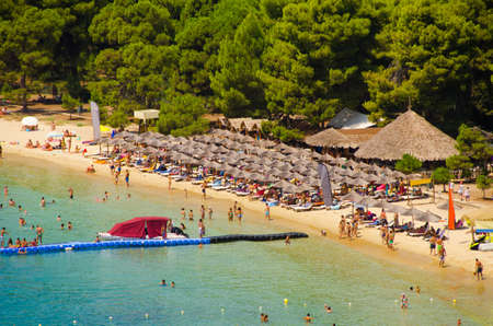 skiathos: Crowded tropical beach with blue water, golden sand, exotic umbrellas and green trees on the background Stock Photo